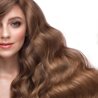 Piękna brązowowłosa dziewczyna o idealnie kręconych włosach i klasycznym makijażu