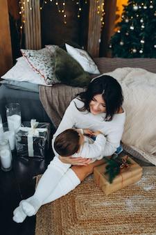 Piękna brązowowłosa mama i piękny syn chłopiec siedzi na podłodze, przytulanie i bawi się