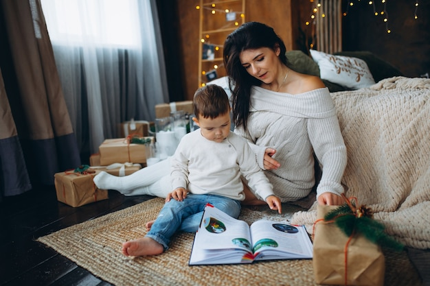 Piękna brązowowłosa mama i śliczny synek siedzą na podłodze i czytają bajki