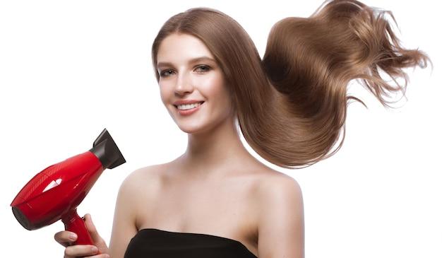 Piękna brązowowłosa w ruchu dziewczyna o idealnie gładkich włosach i klasycznym makijażu.