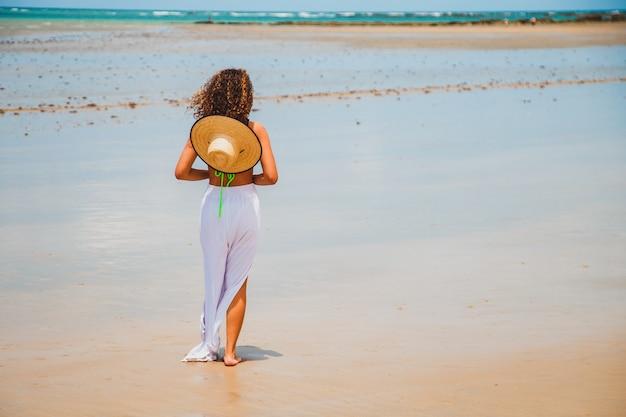 Piękna brazylijska kobieta afro na plaży w rio grande do norte, uśmiechnęła się, czując wolność i fale morza, ciesząc się letnimi wakacjami w cudownym słońcu i cieple
