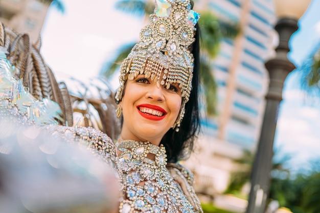 Piękna brazylijska kobieta nosi kolorowy karnawałowy kostium i robi selfie ze swoim smartfonem podczas parady ulicznej carnaval w mieście.