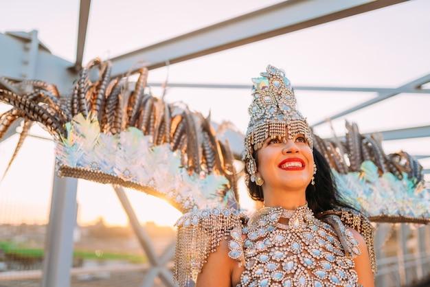 Piękna brazylijska kobieta nosi kolorowy karnawałowy kostium i uśmiecha się podczas parady ulicznej carnaval w mieście.