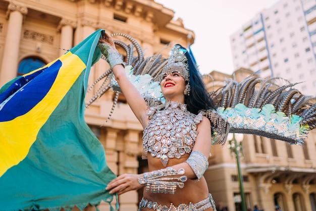 Piękna brazylijska kobieta nosi kolorowy kostium karnawałowy i flaga brazylii podczas parady ulicznej carnaval w mieście.
