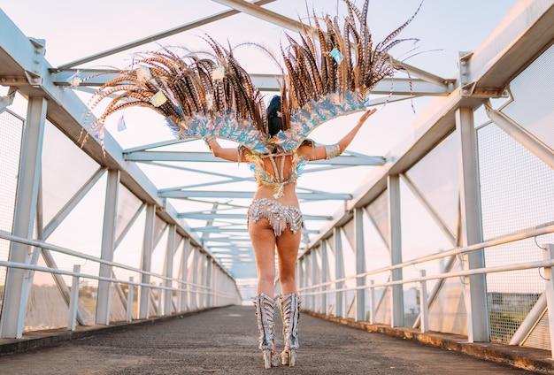 Piękna brazylijska kobieta nosi kolorowy kostium karnawałowy z powrotem podczas parady ulicznej carnaval w mieście.