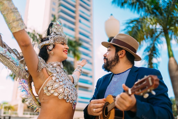 Piękna brazylijska kobieta ubrana w kolorowy karnawałowy kostium i samba grający na brazylijskim instrumencie podczas parady ulicznej carnaval w mieście.