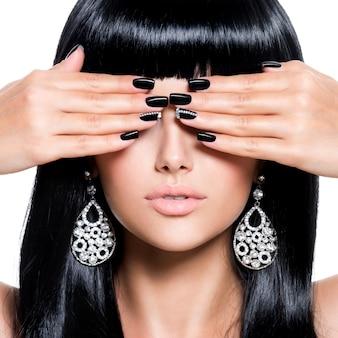 Piękna brunet kobieta z czarnymi paznokciami