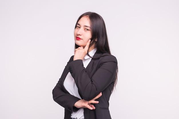 Piękna brunetka azjatka z czerwonymi ustami myśli na białym z miejsca na kopię