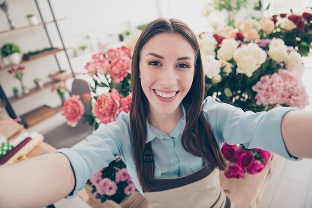 Piękna brunetka botanik pozuje w swojej kwiaciarni