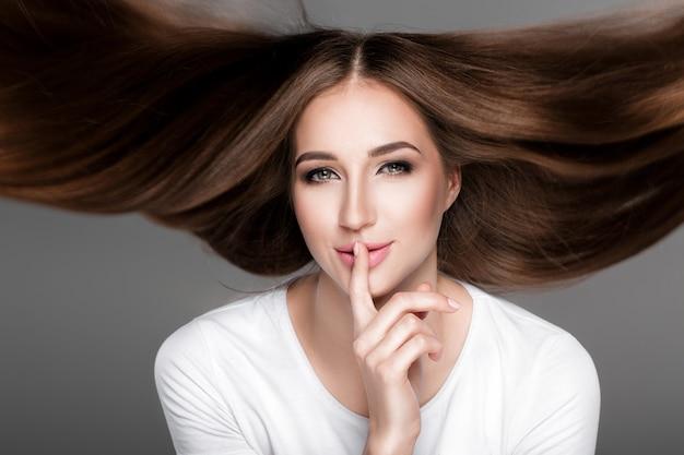 Piękna brunetka dama z przepięknych błyszczących długich włosów latających pokazując gest ciszy. pielęgnacja włosów