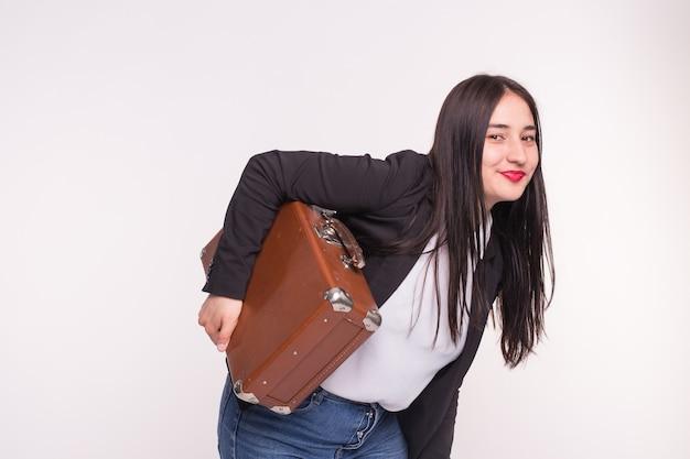 Piękna brunetka dziewczyna azjatyckich trzymając staromodną walizkę na białym tle.