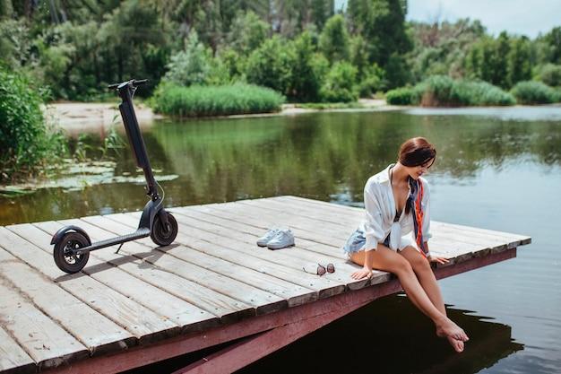 Piękna brunetka dziewczyna odpoczywa na drewnianym moście w pobliżu rzeki obok skutera elektrycznego. pojęcie ekologii i transportu elektrycznego.