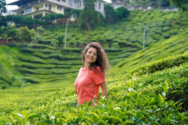 Piękna brunetka dziewczyna pozuje w dolinie herbaty między krzakami zielonej herbaty.