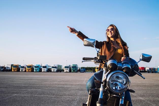 Piękna brunetka dziewczyna siedzi na motocyklu w stylu retro i wskazując palcem w górę
