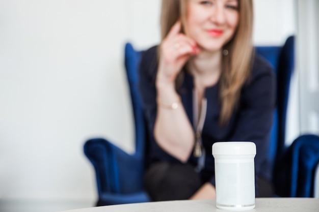 Piękna brunetka dziewczyna siedzi na niebieskim aksamitnym krześle i na lekarstwie, który stoi na stole.
