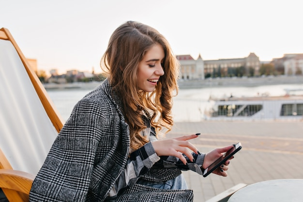 Piękna brunetka dziewczyna sms-y wiadomości, odpoczywając na szezlongu na tle miasta w zimny dzień