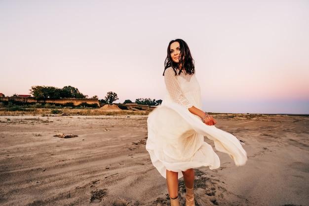 Piękna brunetka dziewczyna w białej sukni na pustyni na tle zachodu słońca. zdjęcie wysokiej jakości