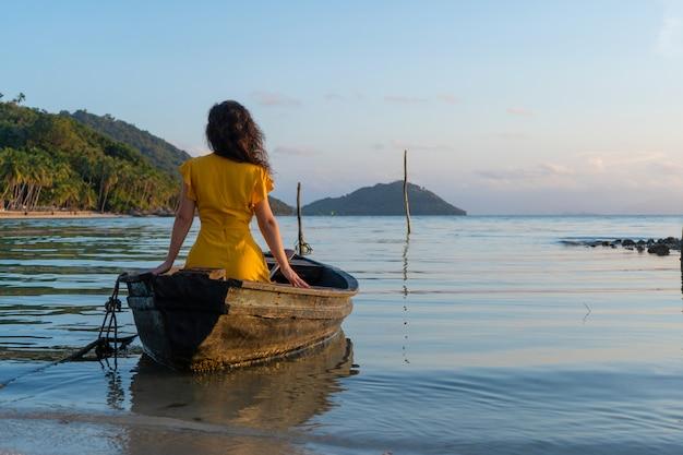Piękna brunetka dziewczyna w żółtej sukience siedzi w starej drewnianej łodzi z widokiem na bezludną tropikalną wyspę. romans na morzu
