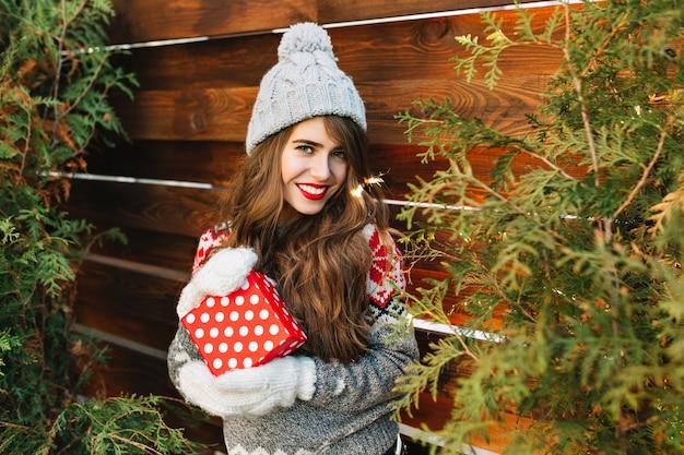 Piękna brunetka dziewczyna z długimi włosami w zimowe ubrania z prezentem na drewnianym zewnątrz. ona się uśmiecha.