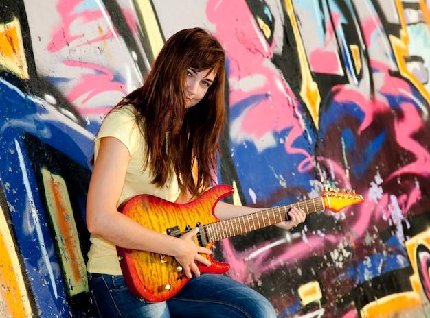 Piękna brunetka dziewczyna z gitarą i graffiti na ścianie