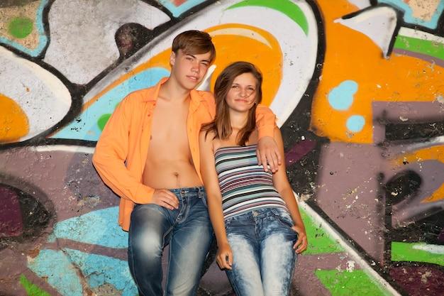Piękna brunetka dziewczyna z gitarą z graffiti na ścianie
