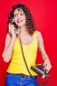 Piękna brunetka dziewczyna z kręcone fryzury pozuje z telefonem w stylu retro