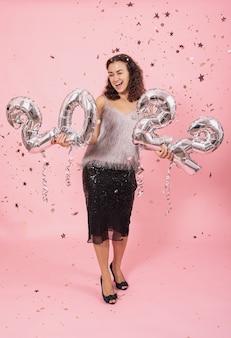 Piękna brunetka dziewczyna z kręconymi włosami i świątecznym stroju pozuje na różowym tle z konfetti i trzyma srebrne balony z numerami 2022.