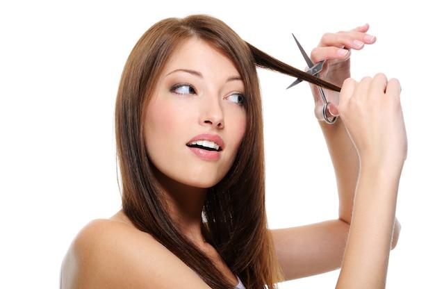 Piękna brunetka dziewczyna z pięknymi długimi prostymi włosami tnąc je nożyczkami