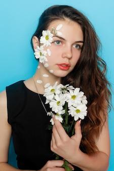 Piękna brunetka dziewczyna z zielonymi oczami makijaż i świeża skóra pozowanie na czerwonym tle z kwiatem, koncepcja pielęgnacji skóry, spa, bio produkt. poziomy