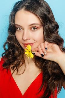 Piękna brunetka dziewczyna z zielonymi oczami makijaż i świeża skóra pozowanie na niebieskim tle z kwiatem, koncepcja pielęgnacji skóry, spa, bio produkt. poziomy