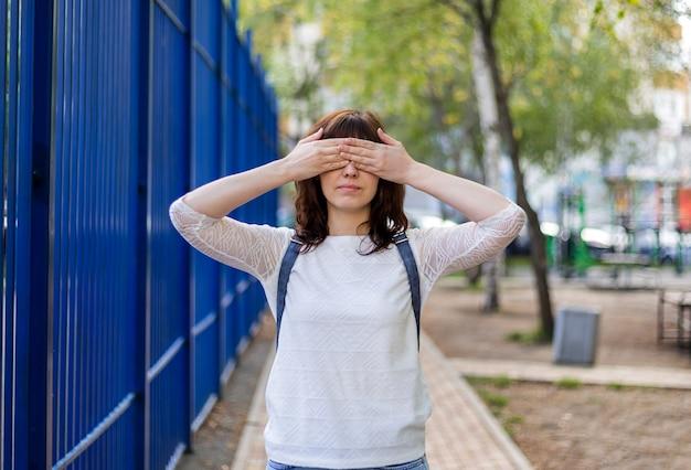 Piękna brunetka dziewczyna zakryła oczy dłońmi. nic nie patrz. ślepota. dziewczyna w białej kurtce stoi na ulicy.