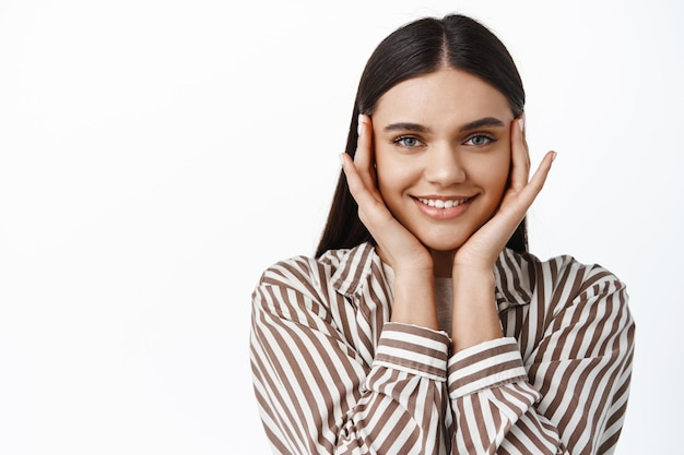 Piękna brunetka dziewczyna ze szczęśliwym uśmiechem, dotykająca twarzy opuszkami palców w pobliżu oczu, używająca kosmetyków do pielęgnacji skóry, aby uzyskać odżywiony efekt twarzy, biała ściana