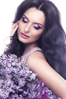 Piękna brunetka dziewczynka z delikatnym romantycznym makijażem, różowymi ustami i kwiatami. piękno twarzy.
