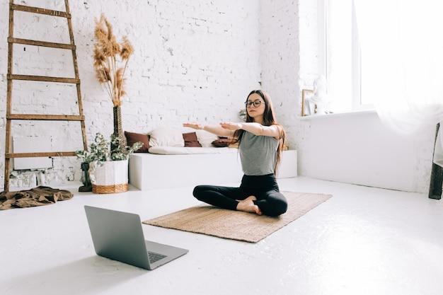 Piękna brunetka fitness kobieta robi ćwiczenia rozciągające przed laptopem robi joga