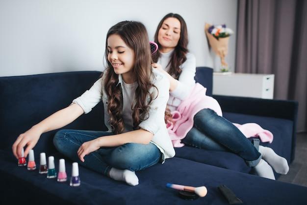 Piękna brunetka kaukaski matka i córka siedzą razem w pokoju. dziewczyna układa kolorowe lakiery do paznokci w jednym rzędzie i bawi się nimi na kanapie. matka siada za nią i szczotkuje dziecięce włosy.