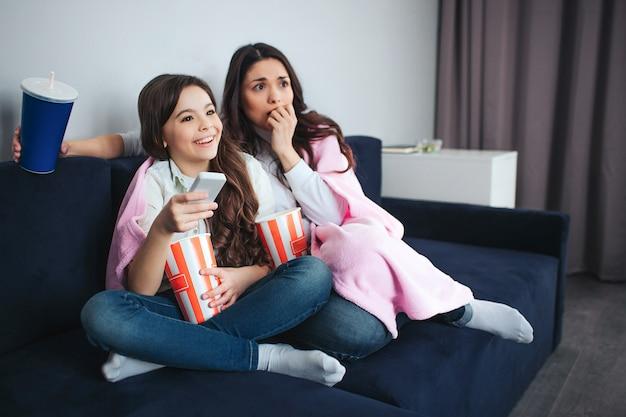 Piękna brunetka kaukaski matka i córka siedzą razem w pokoju. przerażona mama zakrywa usta i oczekuje. ona jest przestraszona dziewczyna trzymać pilota i uśmiech.