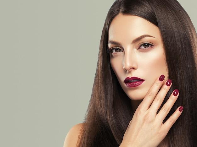 Piękna brunetka kobieta czerwone usta manicure z długimi włosami naturalny makijaż twarzy zbliżenie. strzał studio. kolor tła.