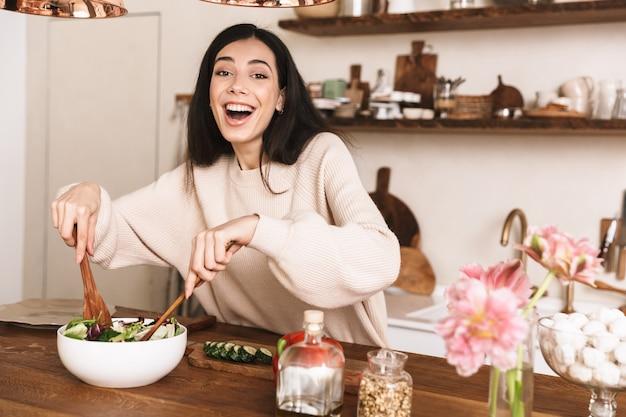Piękna brunetka kobieta gotowanie zdrowej zielonej sałatki z warzywami w stylowej kuchni w domu