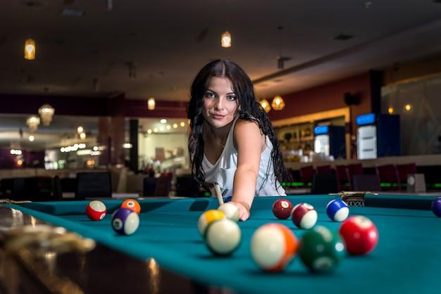Piękna brunetka kobieta gra w bilard w pubie