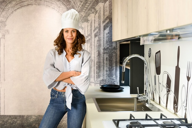 Piękna brunetka kobieta kucharz w białym kapeluszu w kuchni w domu