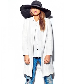 Piękna brunetka kobieta model w dorywczo hipster letnie ubrania na białym tle na białym w czarny duży kapelusz