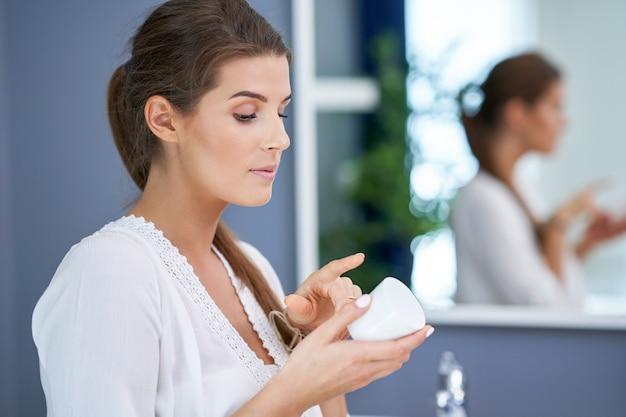 Piękna brunetka kobieta nakłada krem do twarzy w łazience