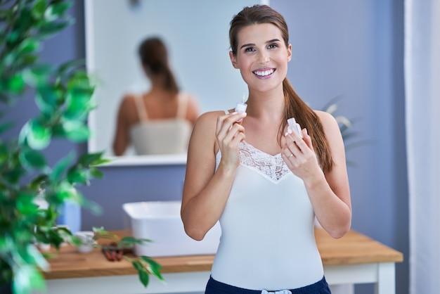 Piękna brunetka kobieta nakłada serum do twarzy w łazience