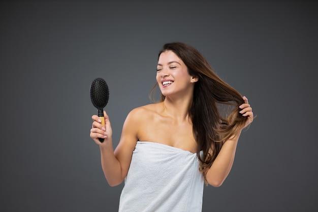 Piękna brunetka kobieta owinięta białym ręcznikiem wokół ciała stoi przed szarą ścianą i śpiewa szczotką do włosów