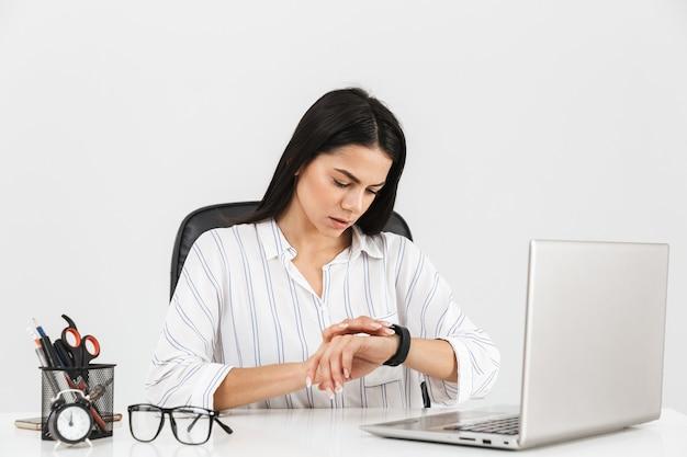 Piękna brunetka kobieta patrząc na zegarek siedząc przy stole z papeterii i pracując na laptopie w biurze na białym tle nad białą ścianą
