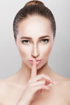 Piękna brunetka kobieta pokazuje gest ciszy. sekret piękna