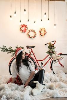 Piękna brunetka kobieta pozuje w świątecznym studiu