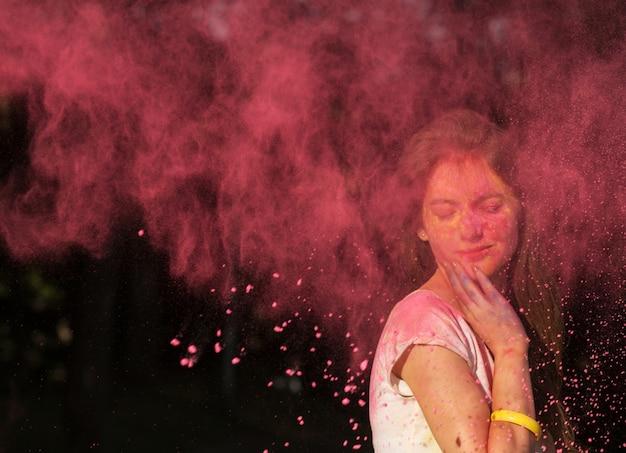 Piękna brunetka kobieta pozuje z różowym proszkiem holi eksplodująca wokół niej