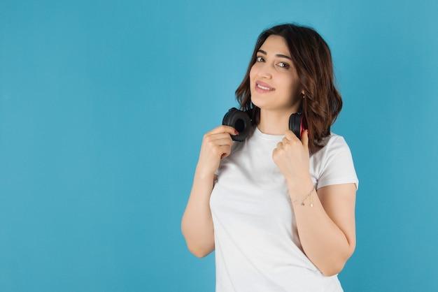 Piękna brunetka kobieta pozuje ze słuchawkami na niebieskiej ścianie