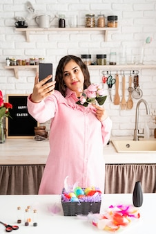 Piękna brunetka kobieta przy selfie przy użyciu telefonu komórkowego w kuchni